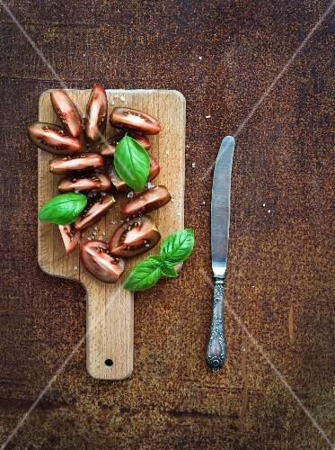 Fresh tomato slices with salt and basil leaves on wooden chopping board