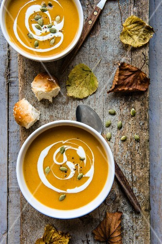 Creamy pumpkin with cream and pumpkin seeds on a wooden board