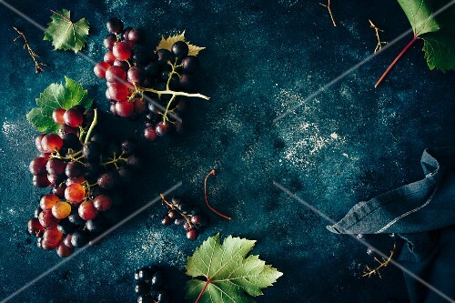 Red grapes with leaves on a dark surface