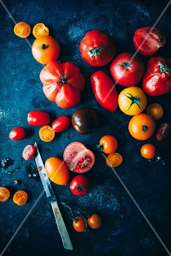 Assorted tomatoes on a dark surface