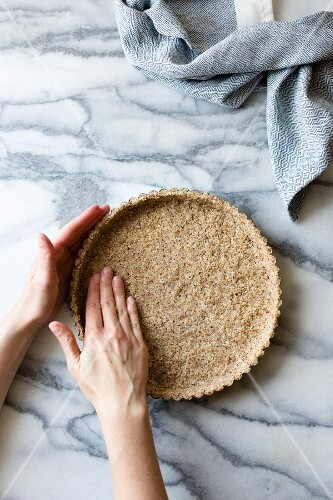 Person prepares a gluten free tart crust, made from sliced almonds, shredded coconut, salt and maple syrup