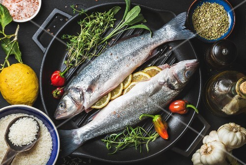 Raw uncooked seabass fish with rice, lemon, herbs and spices on black grilling iron pan