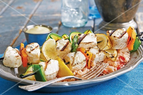 Grilled halibut kebabs with pepper and lemon wedges on a bed of rice