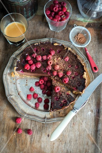 Chocolate tart with chocolate filling and raspberries, decorated with fresh raspberries, sliced
