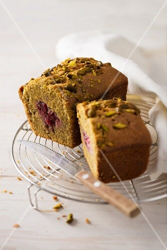 Pistachio and raspberry cake on a cooling rack