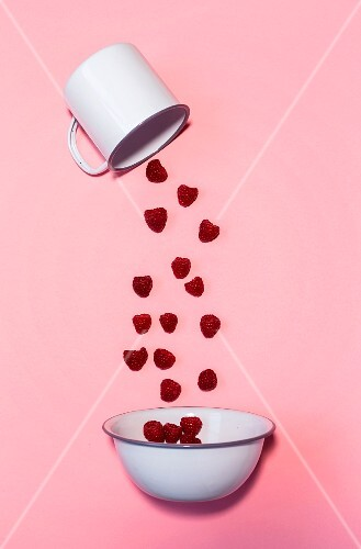 Raspberries falling out of an enamel cup and into a bowl