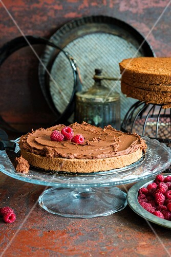 A layer of chocolate sponge with chocolate ganache and raspberries