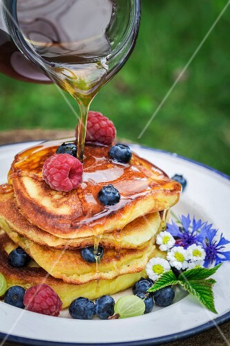 Maple syrup being drizzled on a pile of pancakes with fresh berries