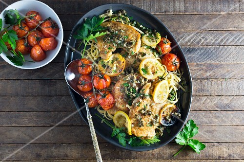 Chicken piccata with tomatoes on a bed of spaghetti