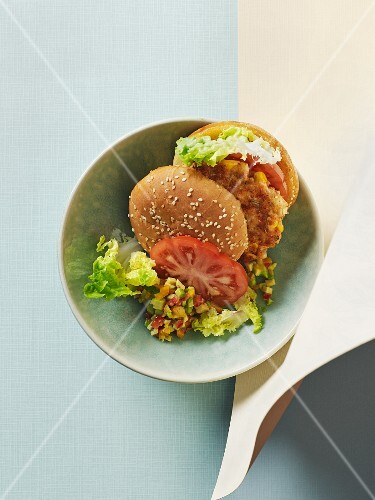 A tofu and salmon burger with tomatoes