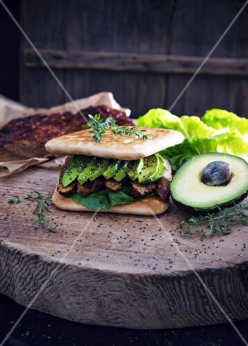 A vegan toasted sandwich with seitan jerky, avocado and chia seeds