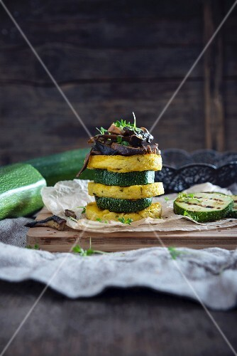 A vegan tower made of polenta rounds and slices of courgette with porcini mushrooms