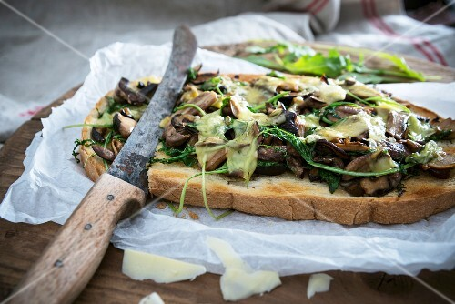 Gratinated toasted bread with wild mushrooms, rocket and cheese (vegan)