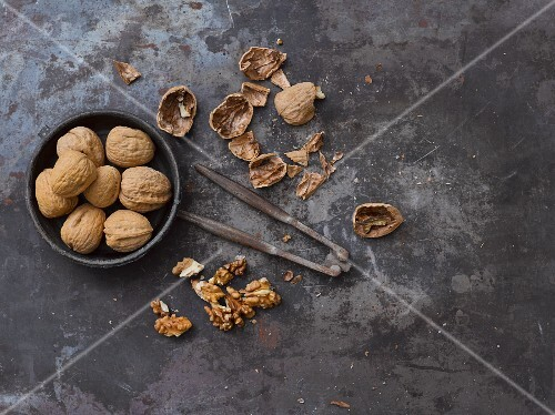 Whole walnuts, nut shells, a nutcracker and walnut seeds