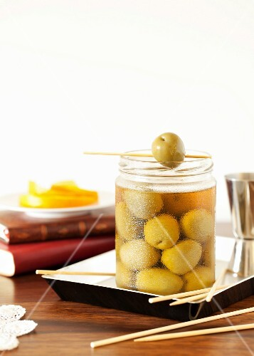 A glass of green olives with wooden skewers