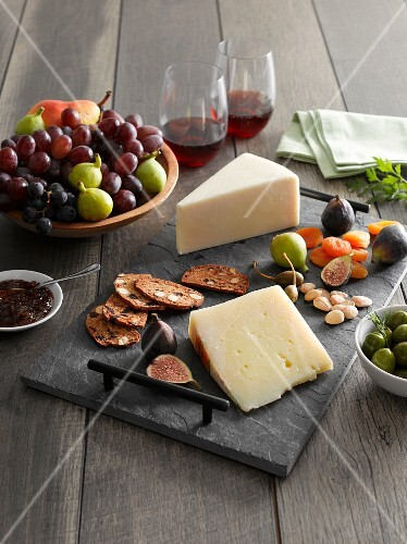 A cheeseboard with fruit, pistachios, fruitcake and olives