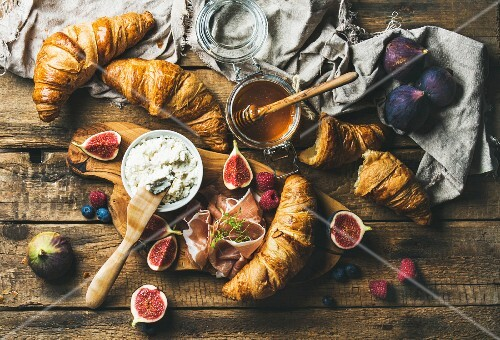 Breakfast with freshly baked croissants, ricotta cheese, figs, fresh berries, prosciutto di Parma and honey