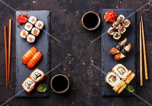 Assorted sushi (Maki and Nigiri) for two on a dark surface