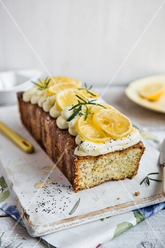 A lemon and poppy seed loaf with cream cheese frosting and rosemary syrup, with a slice removed