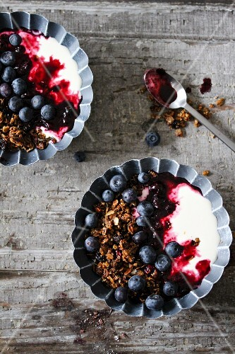 Bowls of blueberry yoghurt with blueberries and granola