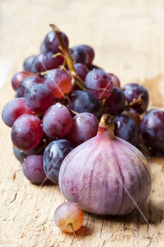 Fresh red grapes and figs on a wooden background