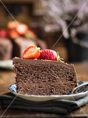 Piece of paleo (floverless and gluten free) chocolate cake with strawberries