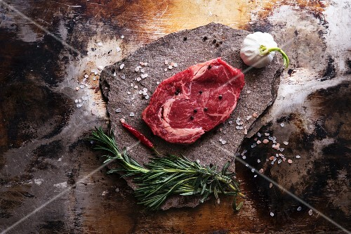 A beef steak, salt, garlic, a chilli pepper and herbs