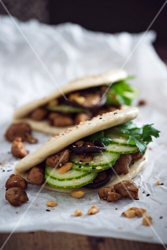 Vegan bao tacos with soya strips, cucumber, shiitake mushrooms, roasted peanuts and sesame seeds