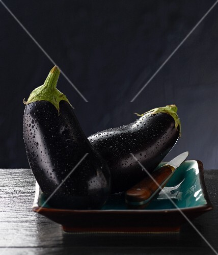Two aubergines on a plate with a knife