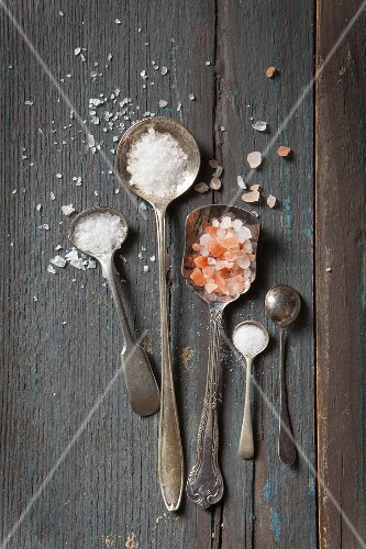 Five vintage mini spoons four filled with different types of salt and one turned over on agrey rustic wooden surface