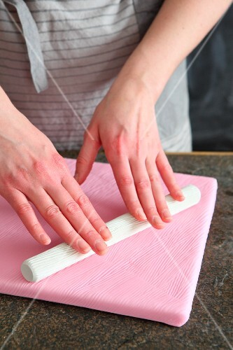Patterns being rolled into soft fondant icing cake board with a textured rolling pin
