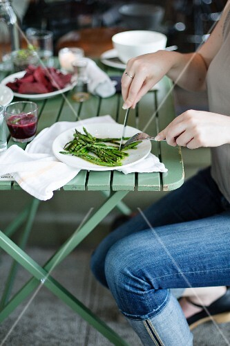 Woman eating blanched green asparagus