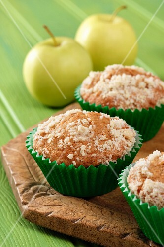 Apple streusel muffins on a wooden board with yellow apples all sitting on a green background.