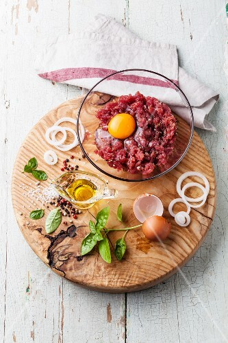 Fresh minced meat with onion and spices in bowl on wooden cutting board on blue background