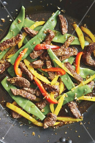 Flash-fried steak strips with colourful vegetables in the wok