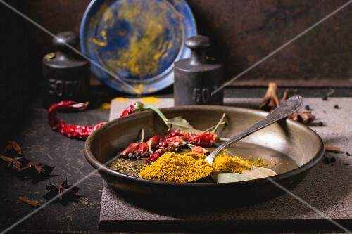 Spices tumeric and dry red hot chili peppers on metal plate