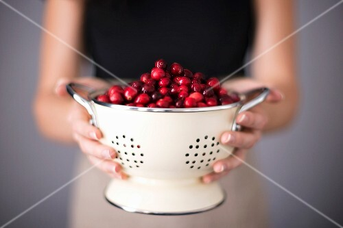 Bright red cranberries in a cream colored strainer being held by a woman