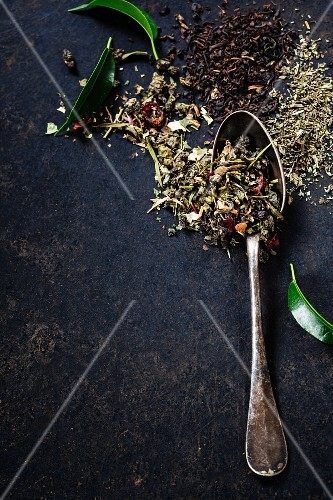 Tea composition with old spoon on dark background