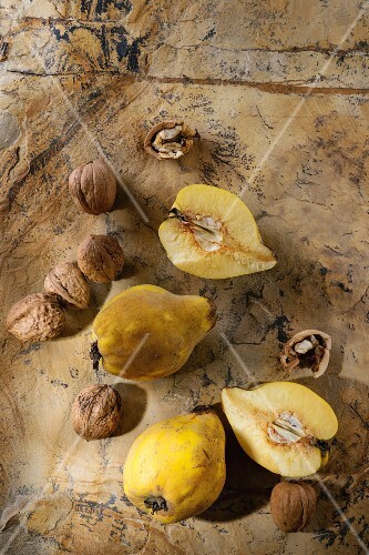 Three whole and cutting juicy quinces with whole and split walnuts over natural brown stone surface