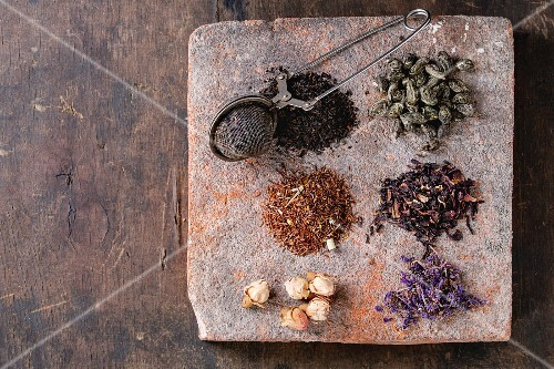 Variety of black, green, rooibos, herbal dry tea leaves and rose buds with vintage strainer on terracotta board