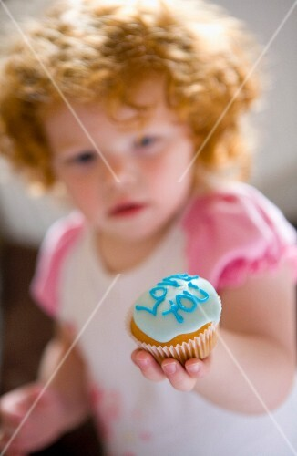 Little girl with red hair holding an iced fairy cake which says I love you