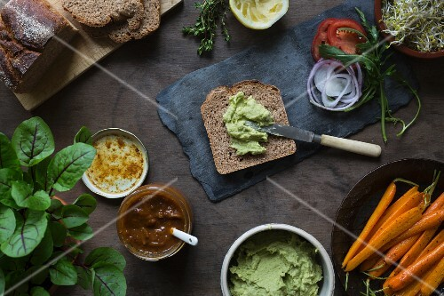 Preparing vegan sandwiches for picnic with roasted carrots, pea spread, and green leafs