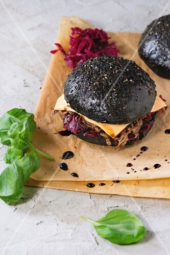 Black burger with beef stews, cheese, red cabbage and balsamic sauce served on baking paper with fresh basil