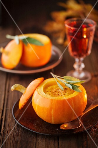 Pumpkin soup in a small pumpkin with leaf of sage