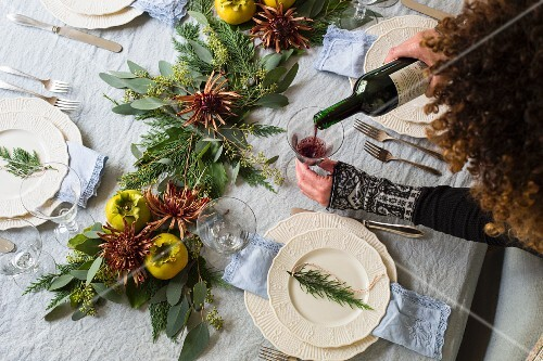 Woman serving red wine on Thanksgiving table setting