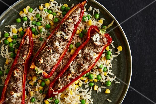 Red pointed pepper filled with minced beef and quark on a bed of rice with sweetcorn and peas