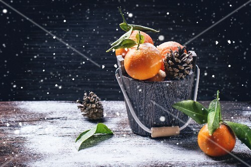 Wooden bucket with tangerines over wooden background with snow and cone