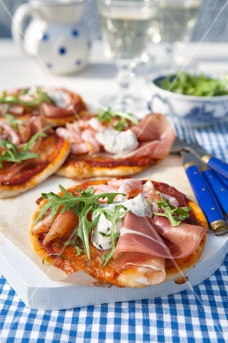 Small pizza with dried ham, tomato sauce, arugula, shrimps, smoked salmon and fresh herbs