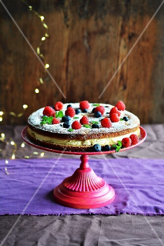 Biscuit cake with forest fruits and cream on a stand
