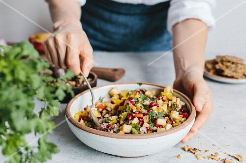 A woman mixing a bowl of peach salsa with walnuts and pomegranate seeds